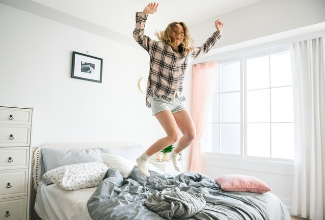 mladá dívka skotačí na posteli