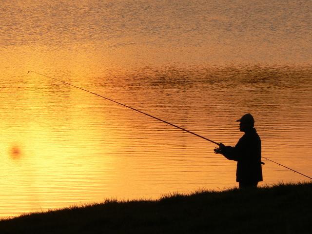 rybář při západu slunce u jezera